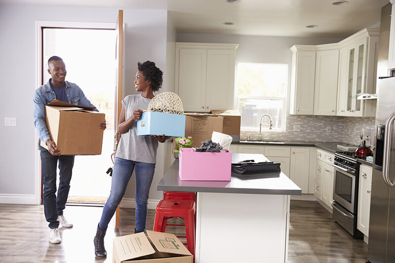 people with boxes moving into a home